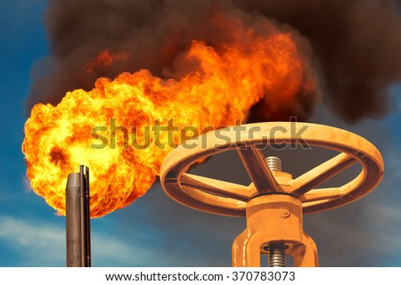 The gas valve on the background of flaming torch flame - stock photo