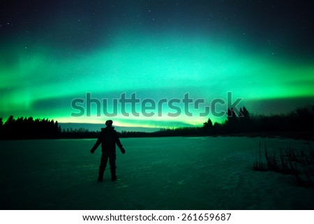 The ghostly colors of the aurora borealis captured above an unidentified person standing on a frozen lake in northern Canada - stock photo