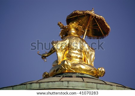 The gilded sculpture at the roof of the Chinese house in the sanssouci royal park in Potsdam in Germany - stock photo