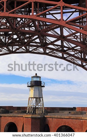 The girders of the Golden Gate Bridge arch over Fort Point Lighthouse. - stock photo