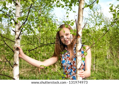 The girl among young birches in the afternoon - stock photo