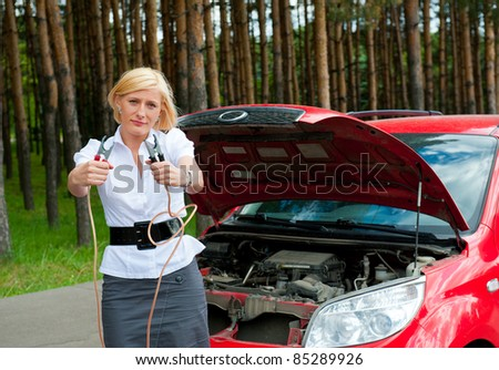 The girl asks for help charge the battery holding cleats - stock photo