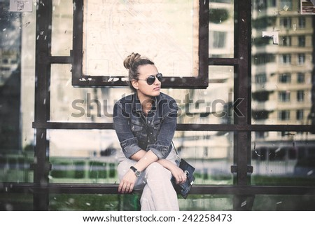 the girl at the bus stop waiting for transport. (pictured present simulation of falling snow) - stock photo