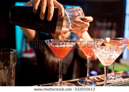 The girl bartender prepares a  cocktail in the nightclub. - stock photo