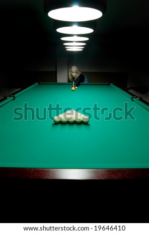 The girl begins a game of billiard - stock photo