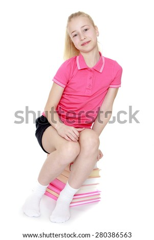 The girl blonde sitting on a pile of books. Isolated on white background. - stock photo