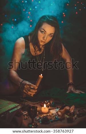 The girl casts a spell with a candle - stock photo