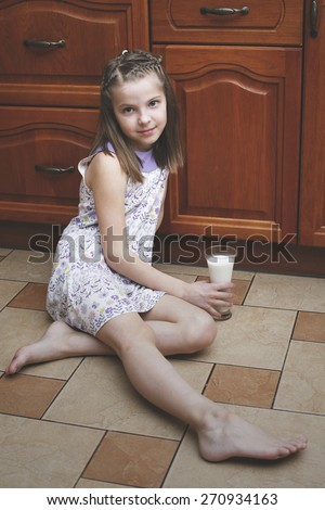 The girl child with a glass of milk sitting on the floor - stock photo