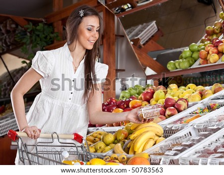 The Girl choose food in supermarket - stock photo