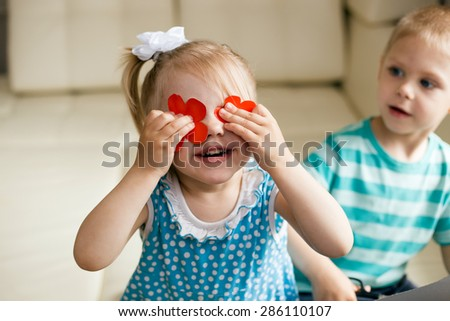 the girl closed her eyes red paper cut outs flowers standing next to the boy and stares at the baby - stock photo