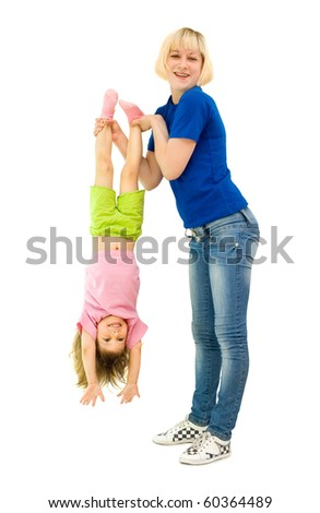 The girl does gymnastics with the child, a white background - stock photo