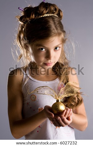 The girl holds a christmas sphere in hands. - stock photo
