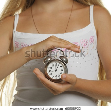The girl holds an alarm clock in hands. It is isolated on a white background - stock photo