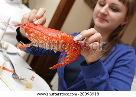 The girl holds cooking lobster in restaurant - stock photo