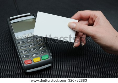 The girl holds in hand a credit card in front of the terminal in shop. A white credit card without image. Payment by a credit card in the terminal - stock photo