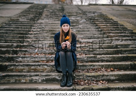 the girl in a blue cap sits on steps in autumn park - stock photo