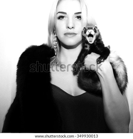 The girl in a fur coat holding a fur animals. The animal in shock on the face of horror - stock photo