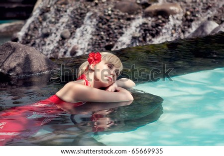 The girl in a red dress lies in water - stock photo