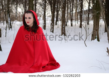 The girl in a red raincoat sit in a winter forest - stock photo