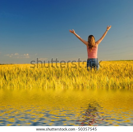 The girl in a wheaten field looks at horizon - stock photo
