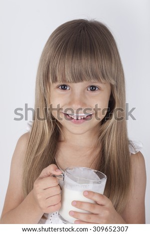 The girl in a white dress drinks milk on a white background.Very cheerful little girl. - stock photo