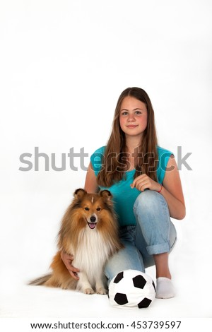 The girl in blue shirt sits next to Shetland Sheepdog on a white background. - stock photo