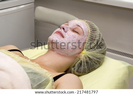 The girl in the beauty salon makes a face mask - stock photo