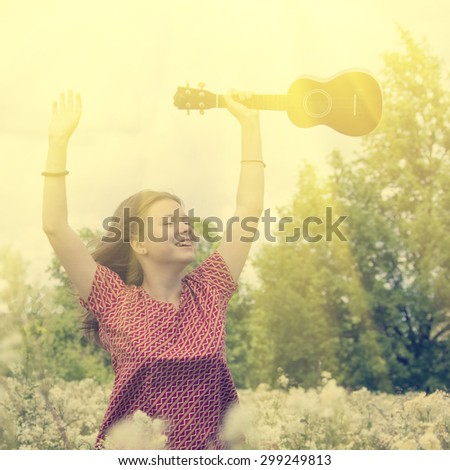 The girl in the early morning walks on the meadow with ukulele - stock photo