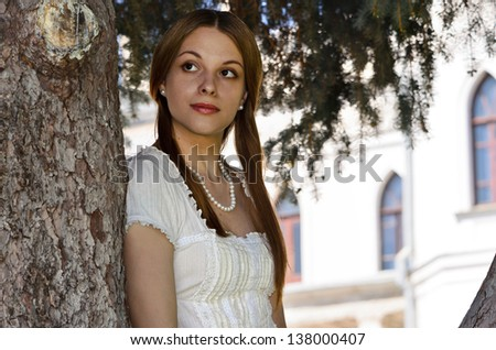The girl in the fairy tale castle on the background of a pine tree - stock photo
