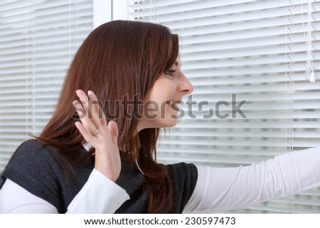 The girl in the office waving her hand to someone in the street - stock photo