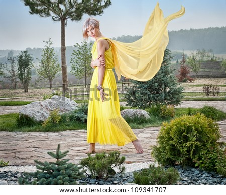 The girl in the park in a yellow dress - stock photo