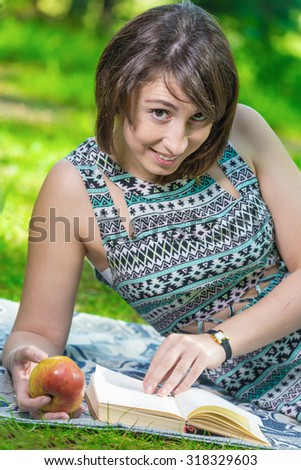 The girl in the Park reading a book - stock photo