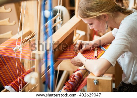 The girl in the production process of textiles are handmade on a loom - stock photo
