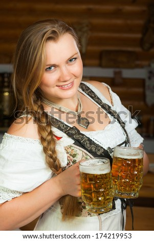 The girl in traditional german uniform holds two beer. - stock photo