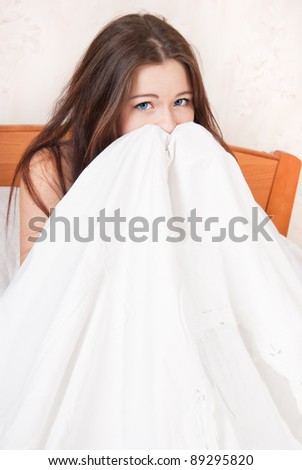 The girl is afraid heavily, hid under a blanket - stock photo