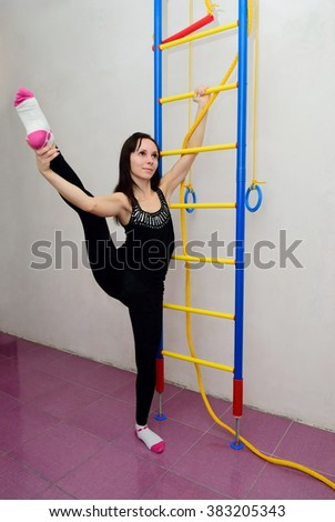 The girl is engaged in gymnastics at home - stock photo