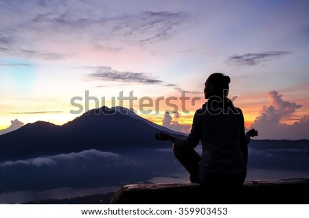 The girl is engaged in yoga and meditation in the mountains at dawn. Mountains of the island of Bali, Indonesia. Stock image. - stock photo