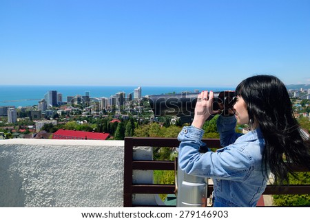 The girl looks at a resort town through a telescope - stock photo