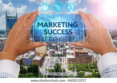 The girl looks at a virtual screen of your Smartphone and see the inscription : marketing success - stock photo