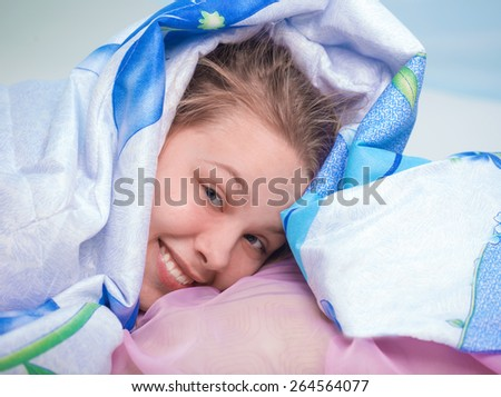 The girl looks from under a blanket - stock photo