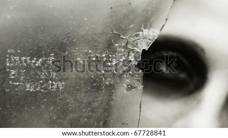 the girl looks through the broken glass - stock photo