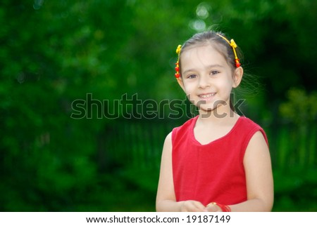 The girl of preschool age against a green lawn with a fence - stock photo