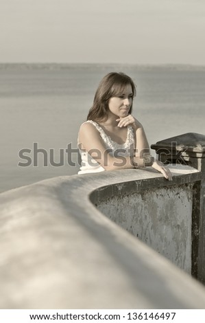 The girl on a pier and looks afar - stock photo