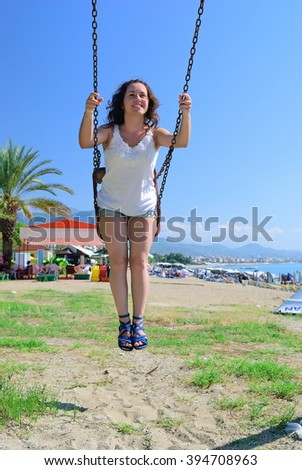 The girl on a swing in summer city - stock photo