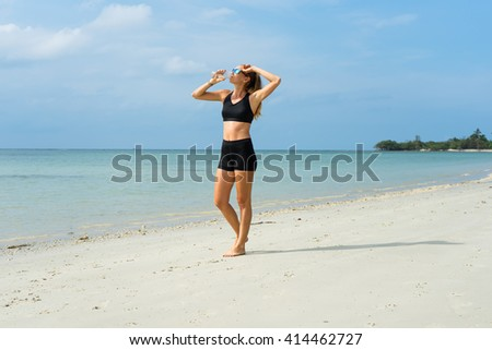 The girl on the beach, the sports girl, in hot weather with a water bottle, dressed in black shorts and an undershirt - stock photo