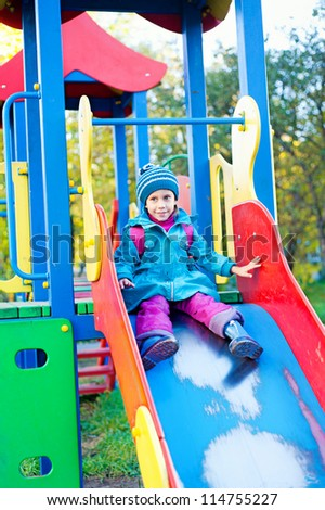 the girl on the playground, slides down a hill - stock photo