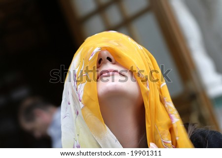 The girl poses with yellow headscarf outdoor - stock photo