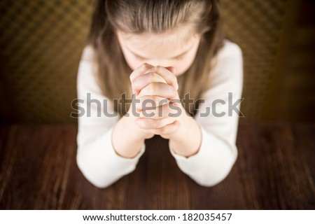 The girl prays at a table - stock photo