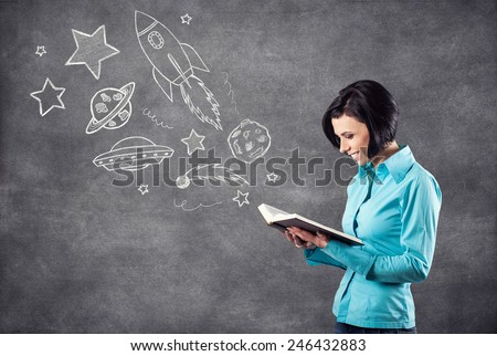 The girl reads the book and dreams about cosmos - stock photo