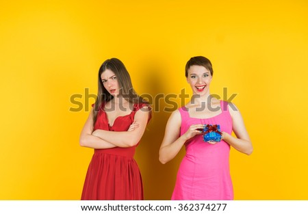 The girl received a gift, and the other girl looks with angry. Isolated studio  yellow background female model. - stock photo